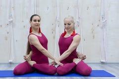 Attraktiva unga sportflickor gör yoga tillsammans grupputbildning sund livsstil för begrepp royaltyfri foto