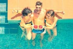 Attraktiva unga vänner som har gyckel i en simbassäng Royaltyfri Bild