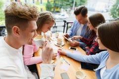 Attraktiva unga vänner som kopplar av på kafét på en suddig bakgrund svart telefon för kommunikationsbegreppsmottagare royaltyfria foton