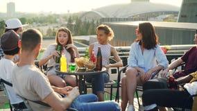 Attraktiva ungdomarsitter för gladlynta vänner på tabellen på taket som talar och dricker öl och coctailar lager videofilmer