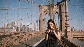 Attraktiva vuxna europeiska kvinnasamtal till vänner som använder den videopd appellen app för smartphone på den Brooklyn bron, N lager videofilmer
