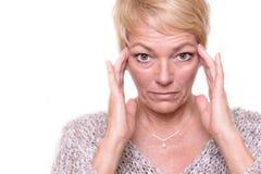 Attraktive ältere blonde Frau, die ihren Teint überprüft Lizenzfreie Stockfotos