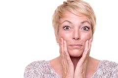 Attraktive ältere blonde Frau, die ihren Teint überprüft Stockfoto