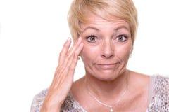 Attraktive ältere blonde Frau, die ihren Teint überprüft Stockfotos