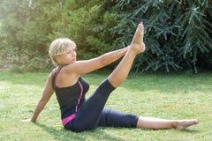 Attraktive ältere blonde Frau in einzelner gerader Beinausdehnungsposition Stockfoto