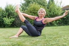 Attraktive ältere blonde Frau, wenn Haltung ausgedehnt wird Lizenzfreie Stockbilder