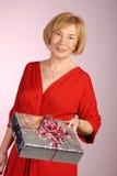 Attraktive ältere Frau, die ein Geschenk anhält Lizenzfreie Stockfotos