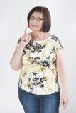 Attraktive ältere Frau droht mit einem Finger Stockbild