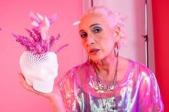 Attraktive ältere weibliche Person, die Blumentopf demonstriert stockbild