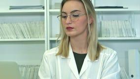 Attraktive Ärztin in den Gläsern unter Verwendung des Laptops, der am Aufnahmeschreibtisch sitzt stock footage