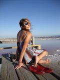 Attraktive 20 etwas Dame sitzt auf einem Pier Lizenzfreie Stockbilder