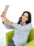 Attraktive Ader-glückliche junge Frau, die ein Tablet nimmt ein Selbstporträt verwendet Stockfoto