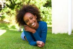Attraktive afrikanische Frau, die auf dem Graslächeln liegt Stockfoto