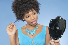 Attraktive Afroamerikanerfrau, die im Spiegel über farbigem Hintergrund betrachtet Lizenzfreie Stockfotografie