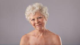 Attraktive alte Frau, die glücklich schaut Stockbilder