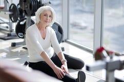 Attraktive anspornende ältere Frau, die in die Turnhalle ausdehnt stockfotos