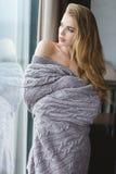 Attraktive anziehende Frau in der grauen Bettdecke, die durch das Fenster schaut lizenzfreie stockfotos