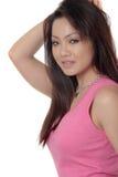 Attraktive asiatische Frau, die im Rosa aufwirft Lizenzfreie Stockfotos