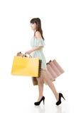 Attraktive asiatische Frau, die mit Einkaufstaschen geht Stockbild