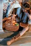 Attraktive böhmische Frau, die auf einem Boden sitzt und Korb betrachtet Lizenzfreie Stockfotografie