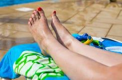 Attraktive Beine, Füße und Zehen auf sunbed Stockbilder