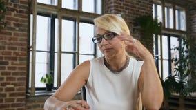 Attraktive beschäftigte Frau in den Gläsern notiert etwas im Tagebuch, das hinter dem Schreibtisch im Büro sitzt zuhause Geschäft stock video footage