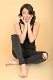 Attraktive besorgte besorgte junge Frau, die auf Boden sitzt stockfotografie