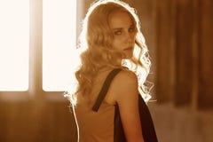 Attraktive blon Frau im schwarzen Kleid Stockfotografie