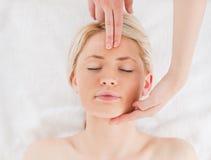 Attraktive blond-haired Frau, die eine Massage erhält Lizenzfreie Stockfotos