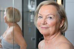 Attraktive blonde ältere Frau in einem Badezimmer Stockbild