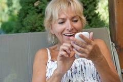 Attraktive blonde ältere Frau mit intelligentem Telefon Stockbild