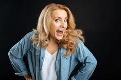 Attraktive blonde Aufstellung mit geöffnetem Mund Stockbilder