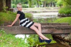 Attraktive blonde Aufstellung nahe dem See Stockbilder