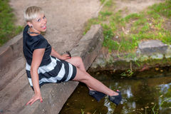 Attraktive blonde Aufstellung nahe dem See Stockfotografie