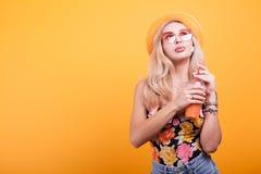Attraktive blonde behaarte Frau, die Orangensaft mit Sonnenbrille zeigt Lizenzfreies Stockbild