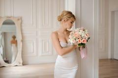 Attraktive blonde Braut im eleganten weißen Kleid, das einen Hochzeitsblumenstrauß hält Stockbilder