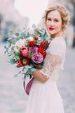 Attraktive blonde Braut mit enormem Blumenstrauß von Rosen und von Pfingstrosen untersucht die Kamera Lizenzfreie Stockbilder
