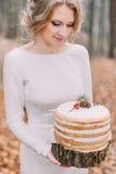 Attraktive blonde Braut mit Hochzeitstorte im Herbstwald Stockbild