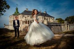 Attraktive blonde Braut mit rotem Lippenstift ist, spinnend tanzend und ringsum nahes ihren Bräutigam am Hintergrund vom alten Stockfoto