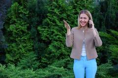 Attraktive blonde Dame, die in der Hand auf Telefon und Griffen es, SMI spricht Stockfotos
