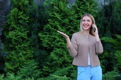 Attraktive blonde Dame, die in der Hand auf Telefon und Griffen es, SMI spricht Lizenzfreie Stockfotografie