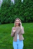 Attraktive blonde Dame, die in der Hand auf Telefon und Griffen es, SMI spricht Stockbilder
