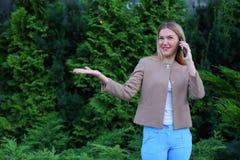 Attraktive blonde Dame, die in der Hand auf Telefon und Griffen es, SMI spricht Lizenzfreie Stockfotos