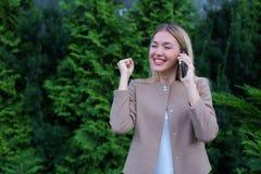 Attraktive blonde Dame, die in der Hand auf Telefon und Griffen es, SMI spricht Lizenzfreies Stockfoto