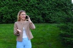 Attraktive blonde Dame, die in der Hand auf Telefon und Griffen es, SMI spricht Lizenzfreies Stockbild