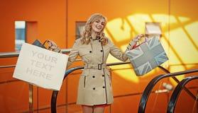 Attraktive blonde Dame, die mit Einkaufstaschen aufwirft Lizenzfreie Stockfotos