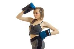 Attraktive blonde Dame im Sport Uniform und Boxhandschuhe, die im Studio aufwerfen Stockbild
