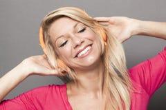 Attraktive blonde Dame mit Kopfhörern Lizenzfreies Stockfoto