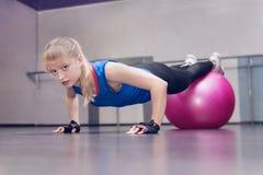 Attraktive blonde Eignung, welche die vorbildliche Ausführung drücken, ups mit rosa fitball an der Turnhalle Gesunder Lebensstil  stockfotografie