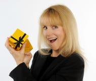 Attraktive blonde Frau öffnet Geschenkbox mit überraschtem Ausdruck Stockbild